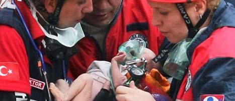 Ett litet barn har räddats ur rasmassorna. Foto: AP/Scanpix