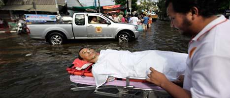 En skadad man tas om hand i Bangkoks förorter. Foto: Altaf Qadri/Scanpix