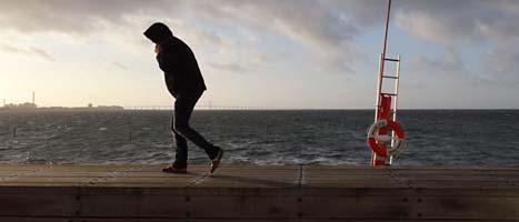En man kämpar mot vinden i Malmö. Den senaste stormen stoppade bland annat trafiken på flera broar. Foto: Johan Nilsson/Scanpix