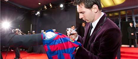 Lionel Messi skriver sin autograf på en tröja före prisutdelningen. FOTO: Alessandro Della Bella/SCANPIX