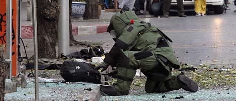 En bombexpert i skyddskläder undersöker en ryggsäck som låg kvar  där bomben sprängdes. Foto. Apichart Weerawong/AP/Scanpix