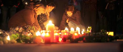 Folk tänder ljus för de som dödades i olyckan. Foto: Maxime Schmid/Scanpix