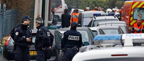Poliser utanför huset där den misstänkte mördaren gömmer sig. Foto: Remy de la Mauviniere/AP/Scanpix
