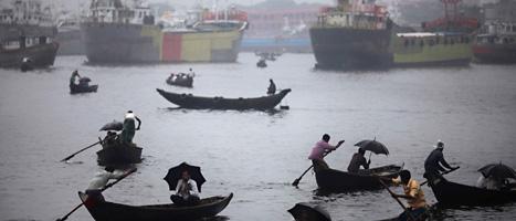 Folk i båtarna i Dhakas hamn har plockat fram paraplyerna.  Regnet har vräkt ner de seanste dagarna. Foto: Saurabh Das/AP/Scanpix