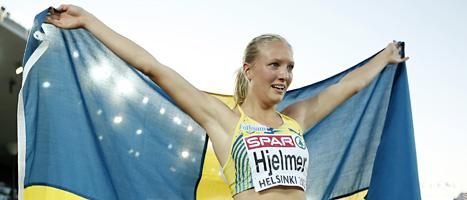 Moa Hjelmner håller upp svenska flaggan för kamerorna efter segern. FOTO: Matt Dunham/SCANPIX