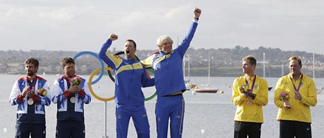 Fredrik Lööf och Max Salminen står högst på pallen och jublar över Sveriges första OS-guld i årets tävlingar. FOTO: Bernat Armangue/SCANPIX