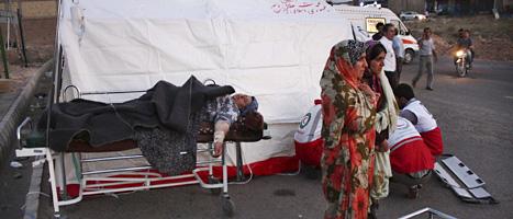 En kvinna ligger skadad på en bår i staden Varzaqan. Minst 300 har dött efter jordbävningar i nordvästra Iran. FOTO: Hamed Nazari/SCANPIX