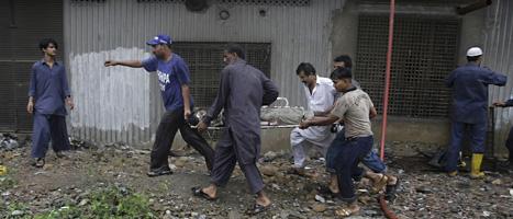 Räddningsarbetare utanför fabriken i Karachi. Foto: Fareed Khan/AP/Scanpix