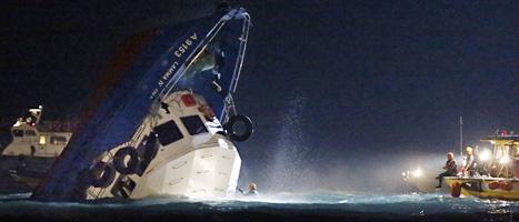 Båten är på väg att sjunka. Fler än trettio människor dog i olyckan i Hongkong. Foto: Kin Cheung/Scanpix.