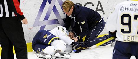 Oscar Sundh ligger på isen efter en hård smäll mot huvudet. Foto: Bror Persson/Scanpix