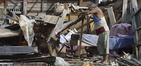 En man på Kuba försöker röja upp i oredan efter stormen Sandy. Foto: Franklin Reyes//Scanpix.