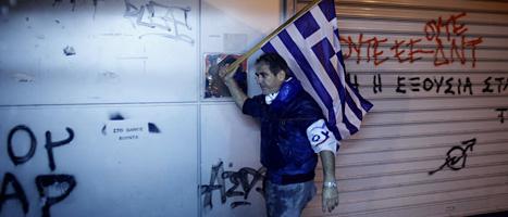 En man med en grekisk flagga protesterar mot regeringen nya sparande.  Foto. Kostas Tsironis/Scanpix.
