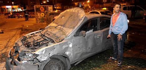 En israelisk man bredvid en bil som skadats av raketer. Foto:Ilan Assayag/Scanpix.