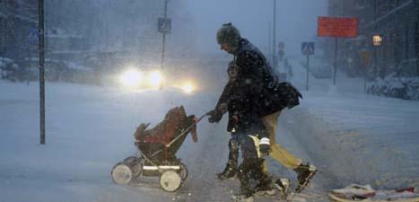 En man med barnvagn i snövädret i Stockholm. Foto: Bertil Enevåg/Scanpix.