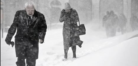 Människor i Stockholm kämpar sig fram i snöovädret. Foto: Anders Wiklund/Scanpix