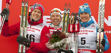 Emil Jönsson i mitten firar en ny seger i världscupen. Till vänster är tvåan Anders Glöersen från Norge och till höger Nikita Kriukov från Ryssland. Foto: Jeff McIntosh/Scanpix