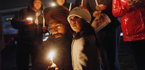 En pappa och ett barn tänder ljus för att minnas dem som sköts ihjäl i en skola i USA. Foto: Jason DeCrow/Scanpix