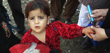 En pojke i Pakistan har fått vaccin mot polio. En vårdare ritar med en penna på pojkens hand så att det ska synas att han har fått vaccin. Foto: K.M. Chaudary/Scanpix