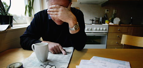 En arbetslös man dricker kaffe och läser annonser om jobb. Foto:Jessica Gow/Scanpix.