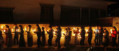 Människor i Nepal har tänt ljus för att hedra munkarna som dött. De protesterar också mot Kinas ledare. Foto: Niranjan Shrestha/Scanpix