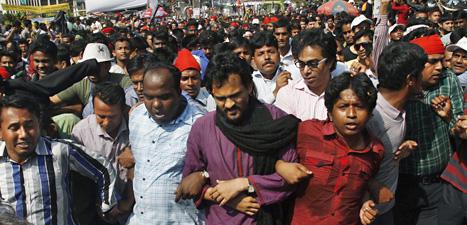 Människor i Bangladesh firar att en islamistisk ledare dömts till döden för krigsbrott. Foto: Riccardo De Luca/Scanpix.
