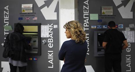 En kvinna står i kö vid en bankomat i Cypern. Foto: Petros Karadjias/Scanpix.