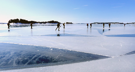 Folk åker skridskor på isen i Stockholms skärgård.  Foto: Lars Pehrsson/Scanpix.