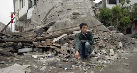 En man sitter vid ett rasat hus i området Sichuan i Kina. Foto: Ng Han Guan/Scanpix.