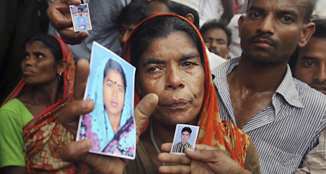 Utanför det rasade huset har människor samlats. De har med sig bilder på människor som är försvunna.Foto: Scanpix