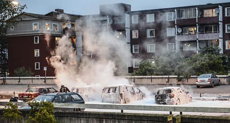 Brandkåren släcker några bilar som ungdomarna tänt eld på.  Foto: Fredrik Sandberg/Scanpix.