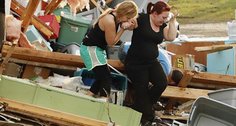 Två kvinnor letar efter en hund som kan ha dödats när virvelstormen förstörde deras hus. Foto: Steve Sisney/Scanpix.