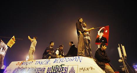 Demonstranter har klättrat upp på taket på en förstörd bil. Foto: Kostas Tsirionis/Scanpix.