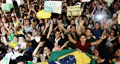 Människor protesterar vid riksdagshuset i Brasiliens huvudstad Brasilia. Foto: Eraldo Peres/Scanpix.
