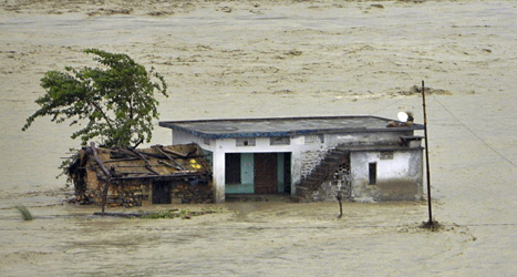 Ett hus har dränkts av vatten när floden Tehsil svämmat över. Foto: AP/Scanpix.