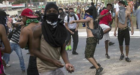 Demonstranter kastar stenar mot poliserna vid fotbollsstadion i Belo Horizonte i Brasilien. Foto: Felipe Dana/Scanpix.
