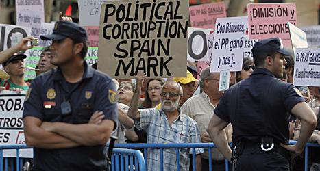 Människor i staden Madrid demonstrerar. De vill att landets regeringschef Mariano Rajoy ska sluta. Foto: Andres Kudacki/Scanpix.