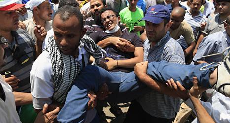 En skadad man får hjälp av sina kamrater. Militärerna sköt och dödade många demonstranter i Egypten i helgen. Foto: AP/Scanpix.