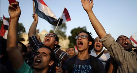 Motståndare mot Egyptens presiden Mohammed Morsi skriker slagord utanför presidentens palats i huvudstaden Kairo på måndagen.