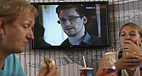 Edward Snowdens ansikte visas på en tv-skärm på flygplatsen i Moskva. Snowden gömmer sig på flygplatsen och hoppas få stanna i Ryssland.