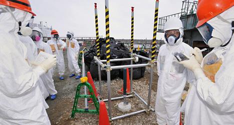 Arbetare i skyddsdräkter tar prov på vatten vid det skadade kärnkraftverket. Foto: Kyodo News /Scanpix