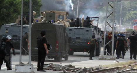 Militärer slänger in tårgas i ett av protestlägren i Kairo innan de går in i det. Foto: AP /Scanpix