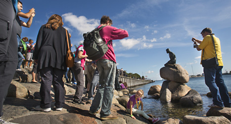 På en sten ute i vattnet sitter den lilla sjöjungfrun. Foto: Drago Prvulovic /Scanpix