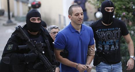 Poliser med masker för ansiktet griper en av politikerna i partiet Gyllene gryning i Grekland. Foto: Kostas Tsironis/Scanpix.