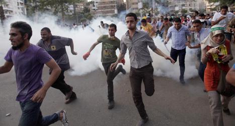 Demonstranter flyr när poliserna sprutat tårgas på dem. Demonstranterna vill att Egyptens valde ledare Muhammad Mursi  ska släppas ur fängelset. Foto: Khalil Hamra/Scanpix.