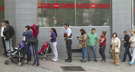 Arbetslösa människor står i kö vid en arbetsförmedling i Spanien. Foto: Paul White/TT.