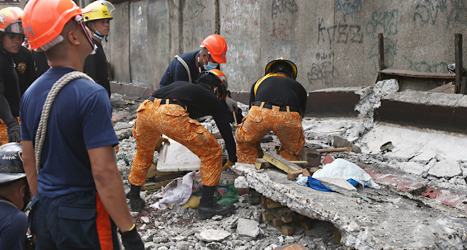 Räddningsarbetare hjälper en man som skadats i jordbävningen i Filippinerna. Foto: AP/TT.