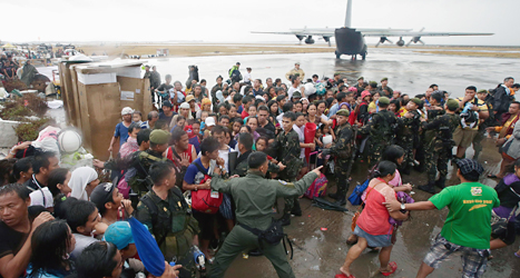 Människor trängs för att försöka komma med flygplanet. De vill bort från den förstörda staden Tacloban där det varken finns mat eller vatten. Foto: Bullit Marquez/TT