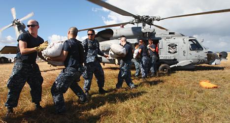 Soldater från USA har kommit fram med hjälp till människor i landet Filippinerna. Foto: Dita Alangkara/TT.