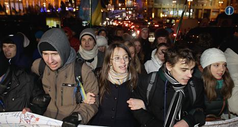 Människor i Ukraina demonstrerar mot landets regering. Demonstranterna vill att Ukraina ska samarbeta mer med EU. Foto: Sergej Chuzakov/TT.