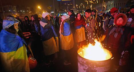 Demonstranter i Kiev värmer sig vid en eld. Foto: Sergej Grits/TT.